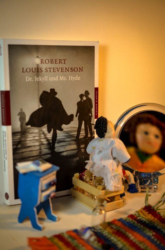 Das Buch von Dr. Jekyll und Mr. Hyde und eine Puppe die sich zu spiegeln scheint